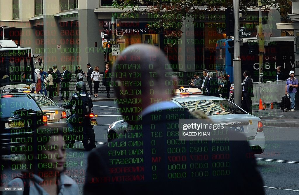 Share rates reflect on the window glass panel of the Australia Stocks Exchange in down town Sydney on May 7, 2013. Australia's central bank cut interest rates to a record low 2.75 percent as investment in the Asia-driven mining sector hits its peak and the persistently high dollar squeezes local industry. The Reserve Bank of Australia's shock decision to slash 25 basis points takes the official cash rate to never-before-seen lows, and is aimed at priming those areas struggling as the economy transforms away from mining. AFP PHOTO / Saeed KHAN