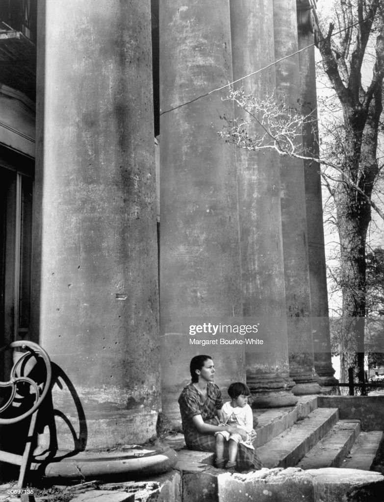 Sharecropper's wife & young daughter sitting on the steps of run-down, nearly abandoned, antebellum mansion in which they rent 2 rooms for $5 a month, on cotton plantation once owned by the late Henry Marston & now belongs to many heirs.