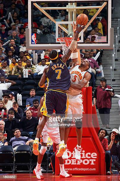 Shareef AbdurRahim of the Atlanta Hawks blocks a shot by Jermaine O'Neal of the Indiana Pacers at Philips Arena on March 22 2003 in Atlanta Georgia...