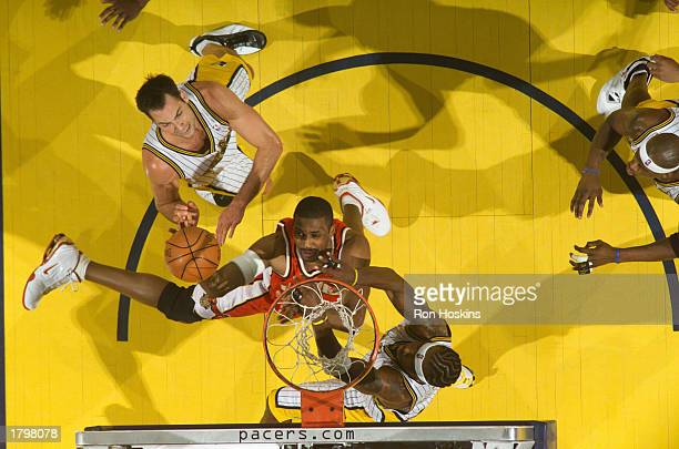 Shareef AdburRahim of the Atlanta Hawks splits Jeff Foster and Jermaine O'Neal of the Indiana Pacers on February 14 2003 at Conseco Fieldhouse in...