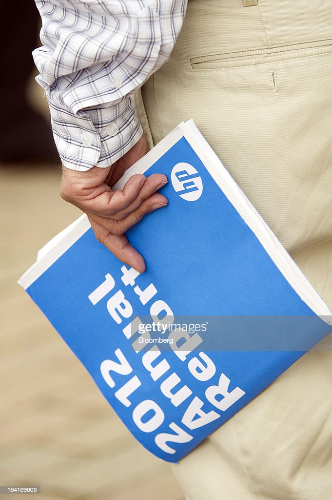 A shareholder carries a Hewlett-Packard Co. annual report as he leaves the company's annual shareholders meeting in Mountain View, California, U.S., on Wednesday, March 20, 2013. Hewlett-Packard Co. Chairman Ray Lane and two other board members were re-elected in slim majorities in a referendum that demonstrates growing dismay over the company's performance and acquisition of Autonomy Corp. Photographer: David Paul Morris/Bloomberg via Getty Images