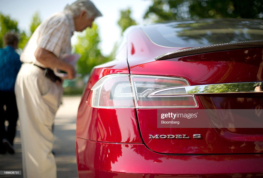 A shareholder examines a Model S sedan after attending the Tesla Motors Inc. annual meeting in Mountain View, California, U.S., on Tuesday, June 4, 2013. Tesla Motors, which has almost tripled in market value this year, can make its electric cars efficiently enough to achieve a gross profit margin almost as high as Porsche AG's, Chief Executive Officer Elon Musk said. Photographer: Noah Berger/Bloomberg via Getty Images