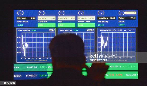 A shareholder of the Deutsche Boerse AG operating the German stock exchange looks at a monitor displaying the charts of German share index DAX and...