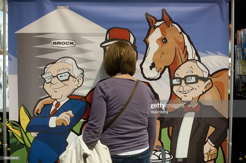 A shareholder places her face through a two-sided backdrop featuring caricatures of Warren Buffett, chairman and chief executive officer of Berkshire Hathaway Inc., left, and Charlie Munger, vice chairman, on the exhibition floor during the Berkshire shareholders meeting in Omaha, Nebraska, U.S., on Saturday, May 4, 2013. Buffett's Berkshire Hathaway Inc.'s cash hoard hit a record as first-quarter profit jumped 51 percent on gains from equity-linked derivatives and insurance operations. Photographer: Daniel Acker/Bloomberg via Getty Images