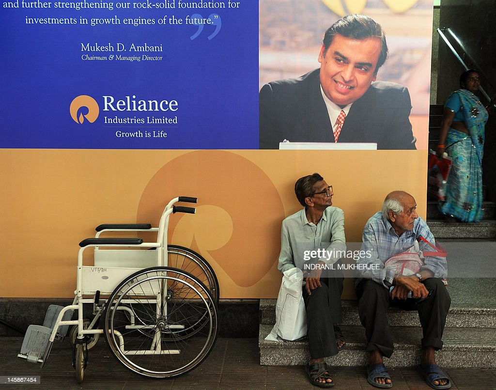 Shareholder sits underneath a poster bearing the portrait of Reliance Industries Limited chairman Mukesh Ambani during the company's annual general meeting in Mumbai, on June 7, 2012. Controlled by the elder of the two Ambani brothers, shares of Reliance Industries are held by one out of every four Indian investors. AFP PHOTO/ Indranil MUKHERJEE