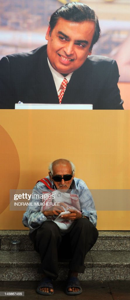 A shareholder sits underneath a poster bearing the portrait of Reliance Industries Limited chairman Mukesh Ambani during the company's annual general meeting in Mumbai, on June 7, 2012. Controlled by the elder of the two Ambani brothers, shares of Reliance Industries are held by one out of every four Indian investors. AFP PHOTO/ Indranil MUKHERJEE