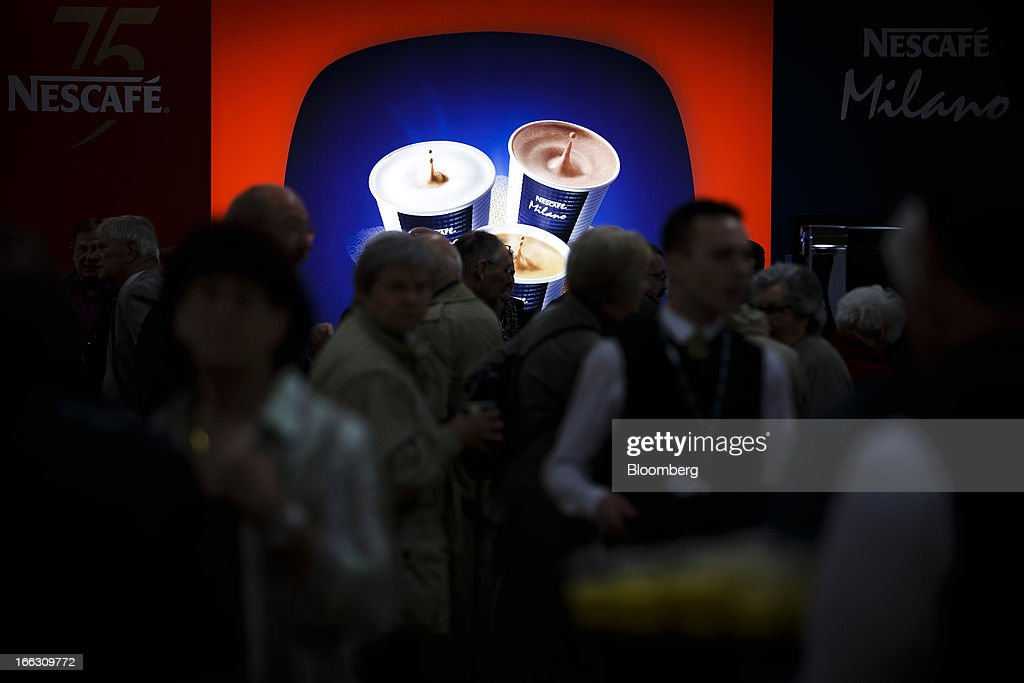 Shareholders pass an illuminated advert for Nestle SA's Nescafe Milano coffee ahead of the company's annual general meeting (AGM) in Lausanne, Switzerland, on Thursday, April 11, 2012. Nestle SA's chairman said Switzerland is becoming more difficult as a business location after voters last month approved some of the world's toughest limits on executives' pay. Photographer: Valentin Flauraud/Bloomberg via Getty Images