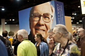 Shareholders surround a large scale portrait of Warren Buffett chairman of Berkshire Hathaway Inc on the exhibition floor during the Berkshire...