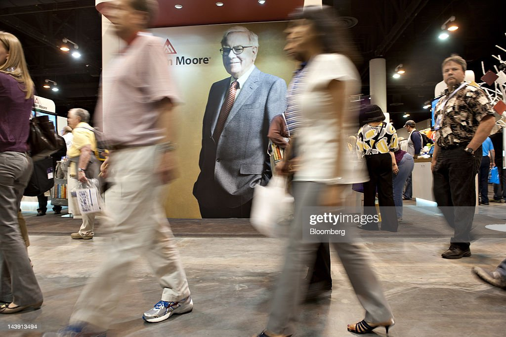 Shareholders walk past an image of Warren Buffett chairman of Berkshire Hathaway Inc during the Berkshire Hathaway annual shareholders meeting in...