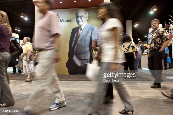 Shareholders walk past an image of Warren Buffett chairman of Berkshire Hathaway Inc during the Berkshire Hathaway annual shareholders meeting in...