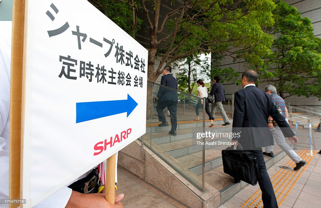 Shareholders walk to enter electric maker Sharp headquarters to attend the annual shareholders meeting on June 25, 2013 in Osaka, Japan. In the meeting President Takashi Okuda apologized for posting a huge annual loss for the second straight year.