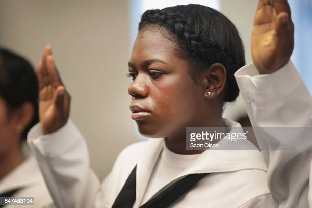 Shari Mahon who was born in Jamaica and is currently serving in the US Navy takes the Oath of Allegiance to become a US Citizen alongside other...
