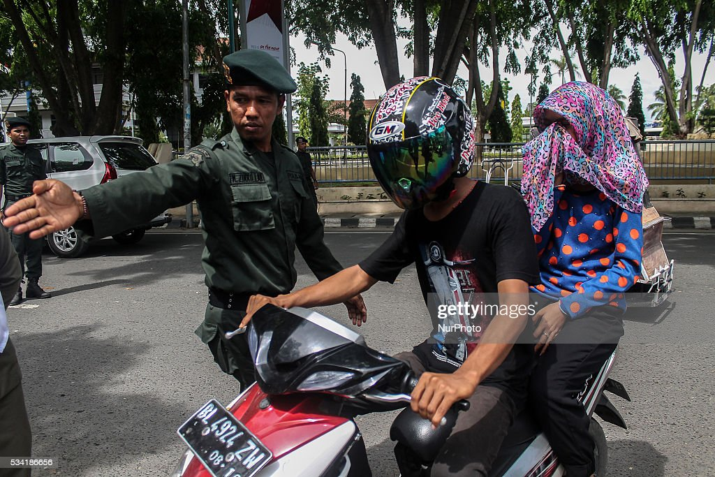 Sharia police intercept a woman motorists on the road in the city of Lhokseumawe, Aceh province, Indonesia on May 25, 2016. During an operation against women wearing tight jeans that is are considered un-Islamic by Islamic sharia law in Aceh. Aceh is the only province of Indonesia that is enforce Islamic Sharia law.