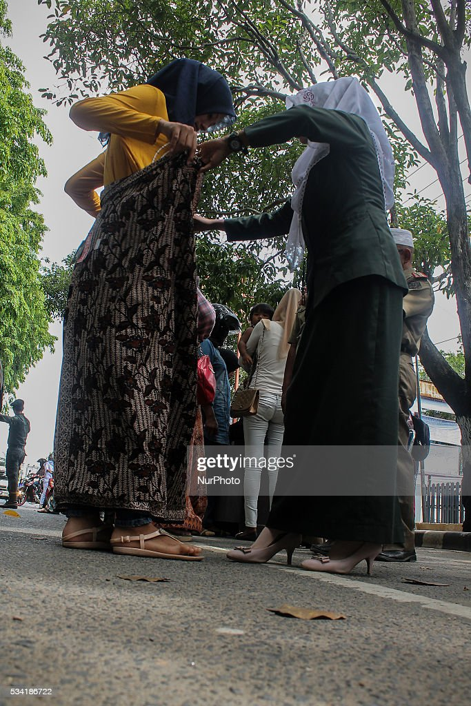 Sharia police put a cloth for women who use tight jeans, in the city of Lhokseumawe, Aceh province, Indonesia on May 25, 2016. During an operation against women and men that wearing clothing that is are considered un-Islamic by Islamic sharia law in Aceh. Aceh is the only province of Indonesia that is enforce Islamic Sharia law.