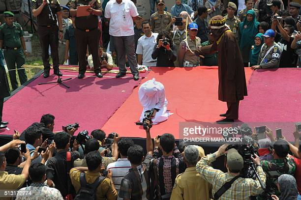 TOPSHOT A sharia policeman canes a woman for breaking Islamic law during a public punishment in Banda Aceh on March 1 2016 The woman who had been...