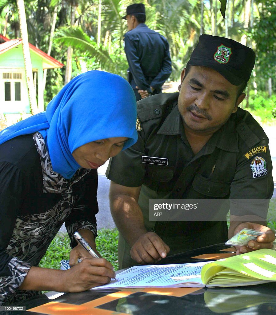 A Sharia policeman looks as a woman signs a sheet declaring that she was inappropriately dressed, during a village raid against women wearing tight pants and clothing in Lambalek in West Aceh district in Aceh province on May 25, 2010. Local authorities are implementing Sharia (Islamic) law, which has been adopted by the provincial government and which stipulates that women can only show their face and their hands, according to sharia police officials. Aceh province runs under special autonomy and is one of the most conservative regions in the mainly Muslim archipelago having established a religious police force.
