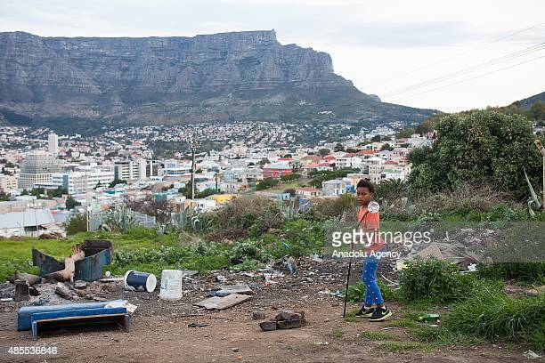 Sharida Rex who live in a tin house near the city's oldest cemetery Tana Baru plays outside her house in Cape Town South Africa on August 22 2015