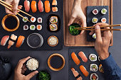 Top view of couple hands eating sushi food at japanese restaurant. High angle view of woman hand serving seaweed in little bowl with sesame to man while holding hosomaki with chopsticks. Couple eating