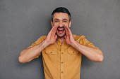 Happy mature man holding hands around mouth and shouting while standing against grey background