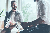 Cropped image of two young businessmen in smart casual wear talking and smiling while sitting on the window sill in office