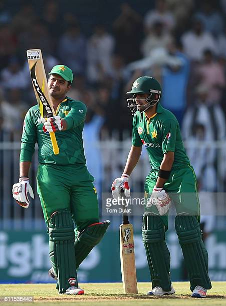 Sharjeel Khan of Pakistan celebrates scoring 50 with Babar Azam during the first One Day International match between Pakistan and West Indies at...