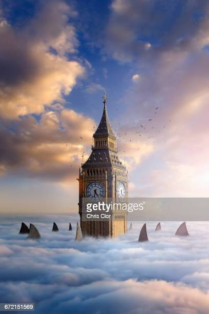 Shark fins and birds circling clock tower above clouds