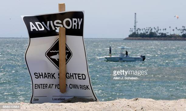 A shark sighting advisory is posted on the beach as researchers from California State University Long Beach Marine Biology try to locate sharks amid...