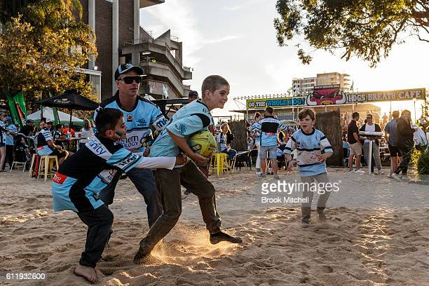 Sharks fans at Southern Cross Group Stadium play on a fake beach installed for the night of the 2016 NRL Grand Final on October 2 2016 in Sydney...