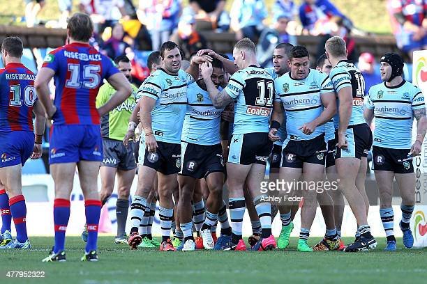 Sharks team mates celebrate a try with Knights players looking dejected in frame during the round 15 NRL match between the Newcastle Knights and the...