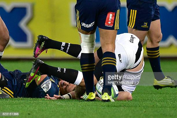 Sharks' Willie Le Roux lands on his neck after a midair tackle by Highlanders' Jason Emery earning Emery a red card during the Super Rugby match...