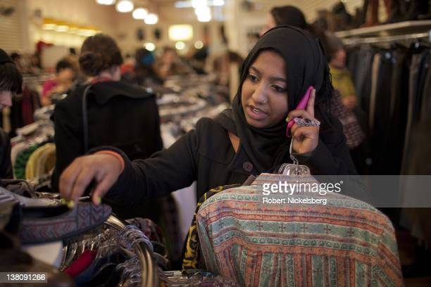 Sharmin Hossain a 20 year old BangladeshiAmerican speaks on her cell phone while shopping January 2 2012 in a thrift store in Brooklyn New York