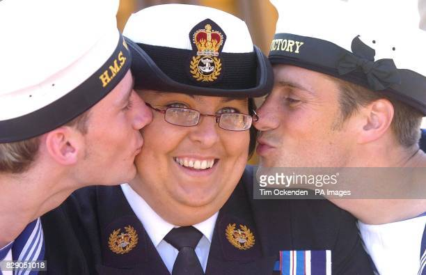 Sharon Hall from Fareham near Portsmouth who is a MasteratArms in the Royal Navy celebrates with two models on board Nelson's flagship HMS Victory...