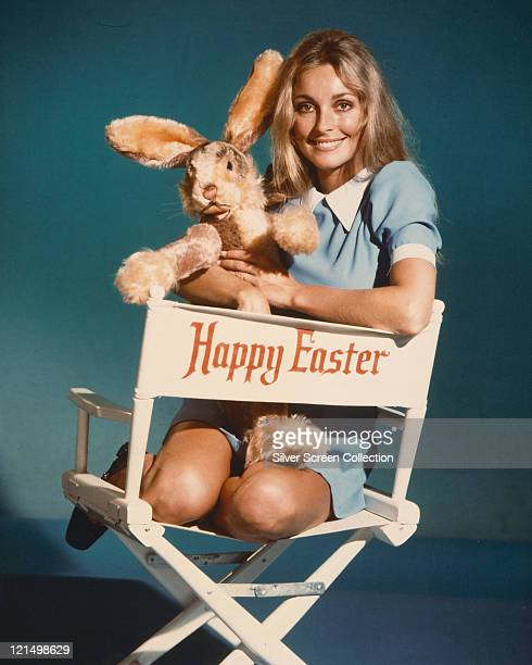Sharon Tate US actress wearing a blue dress with a white collar holding a toy rabbit and sitting in a director's chair with the legend 'Happy Easter'...