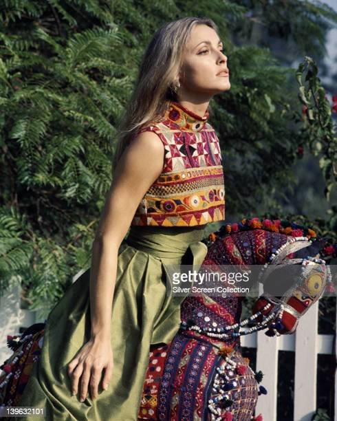 Sharon Tate US actress wearing multicoloured shortsleeved top and a long green skirt as she sits astride a toy horse circa 1965
