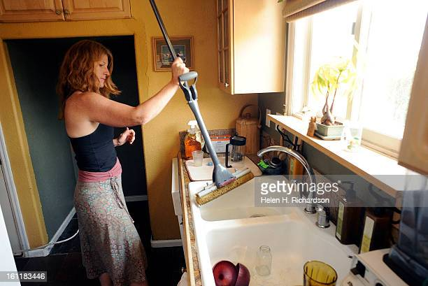 SharonDocherty rinses out a mop as she begins to clean the floor behind the refrigerator at her home in Mill Creek Estates She and her family were...