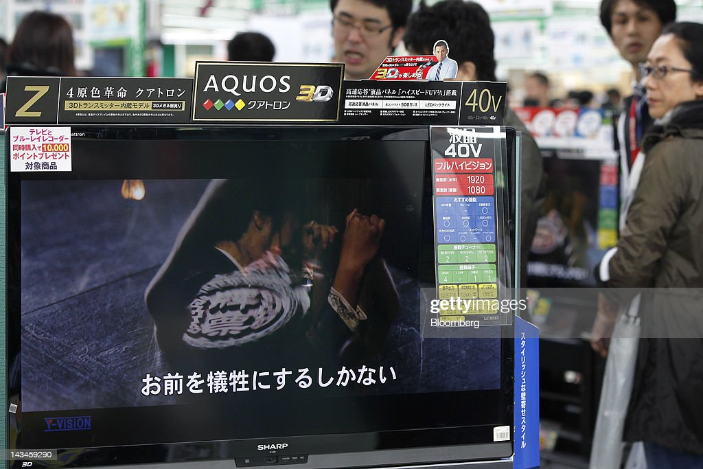 A Sharp Corp. Aquos liquid crystal display (LCD) television is displayed as customers look through televisions at the Labi Ofuna electronics store, operated by Yamada Denki Co., in Yokohama City, Kanagawa Prefecture, Japan, on Friday, April 27, 2012. Sharp Corp., Japan's biggest maker of LCD panels, forecast a net loss wider than analyst estimates as falling TV prices prompted the company to turn to Foxconn Technology Group for investment. Photographer: Kiyoshi Ota/Bloomberg via Getty Images