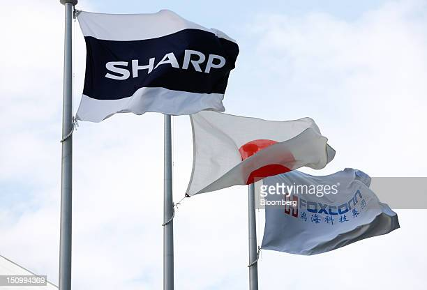 A Sharp Corp flag left Japanese national flag center and Foxconn Technology Group flag fly outside the Sakai Display Products Corp plant in Sakai...