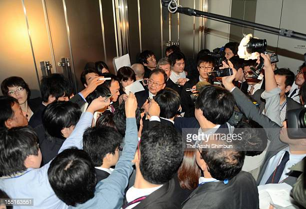 Sharp Corp President Takashi Okuda is surrounded by media reporters after the midyear financial result press conference on November 1 2012 in Tokyo...
