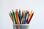 Sharpened colored pencils in pencil holder, on white background.