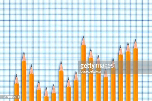 Sharpened pencils forming bar chart on blue graph background : Stock Photo