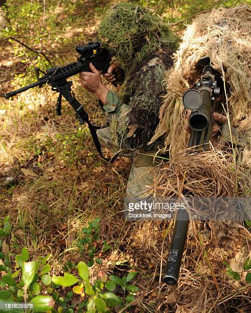Sharpshooters sneak through the forest in their ghillie suits.