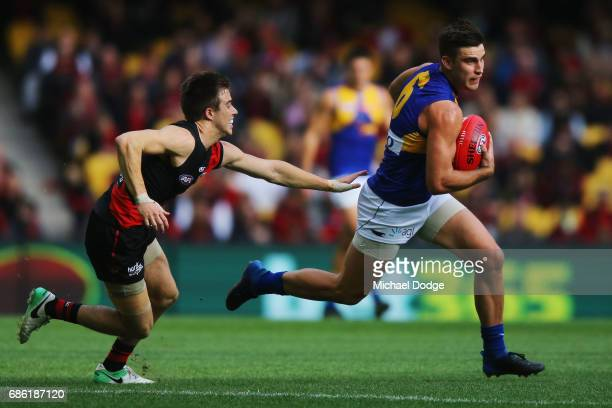 Sharrod Wellingham of the Eagles runs with the ball away from Zach Merrett of the Bombers during the round nine AFL match between the Essendon...