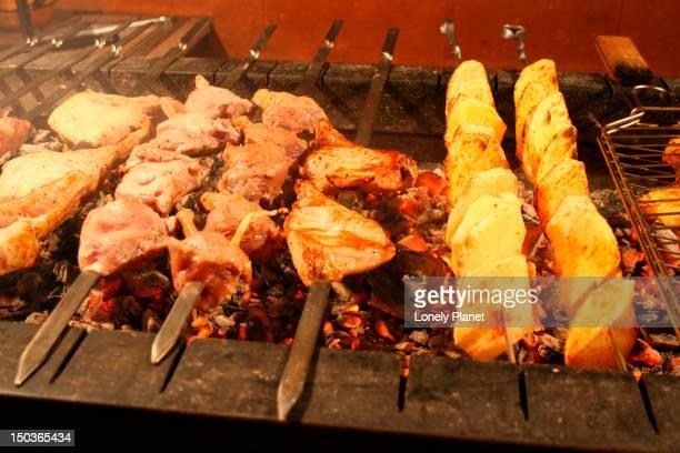 Shashliks cooking over hot coals at Noah's Arc restaurant.