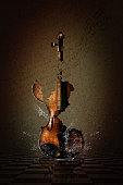Shattered Violin with water splashes amidst a dark grungy scene.
