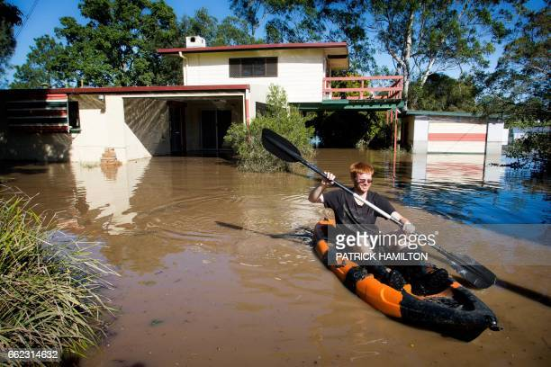 Shaun Adams uses a kayak to paddle out of his home partially submerged under floodwaters caused by Cyclone Debbie in North MacLean Brisbane on April...