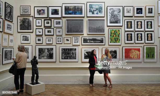 Shaun Boyle and Aly Garvey look at art work during the press view of the Royal Academy summer exhibition Burlington House London