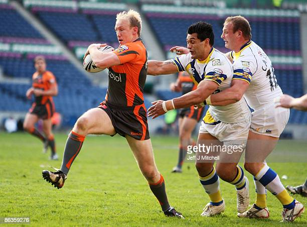 Shaun Briscoe of Hull KR breaks through the tackle from Paul Rauhihi and Gareth Carvell of Warrington during the Super League Magic Weekend match...