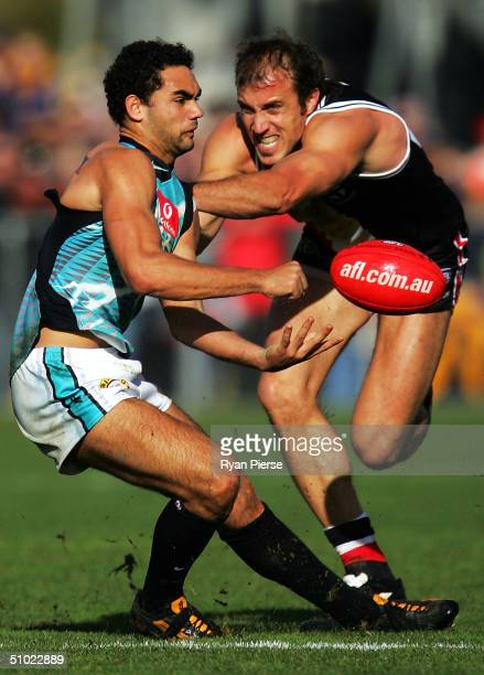 Shaun Burgoyne for the Power gets a handball away despite pressure from Fraser Gehrig for the Saints during the round fourteen AFL match between The...