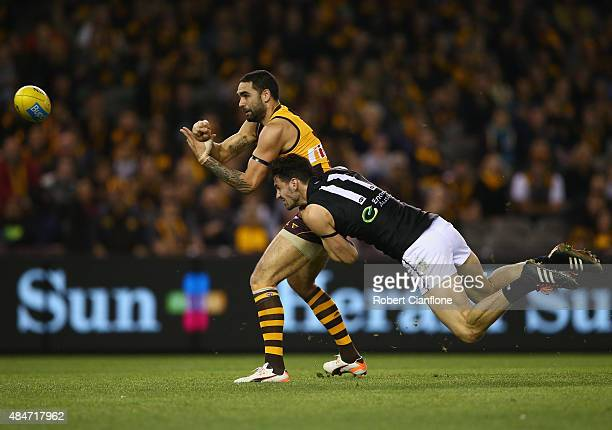 Shaun Burgoyne of the Hawks gets his handball away from John Butcher of Port Adelaide during the round 21 AFL match between the Hawthorn Hawks and...