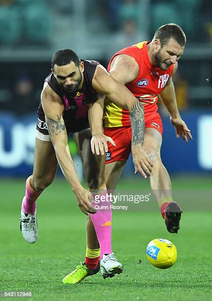 Shaun Burgoyne of the Hawks smouthers a kick by Mitch Hallahan of the Suns during the round 14 AFL match between the Hawthorn Hawks and the Gold...